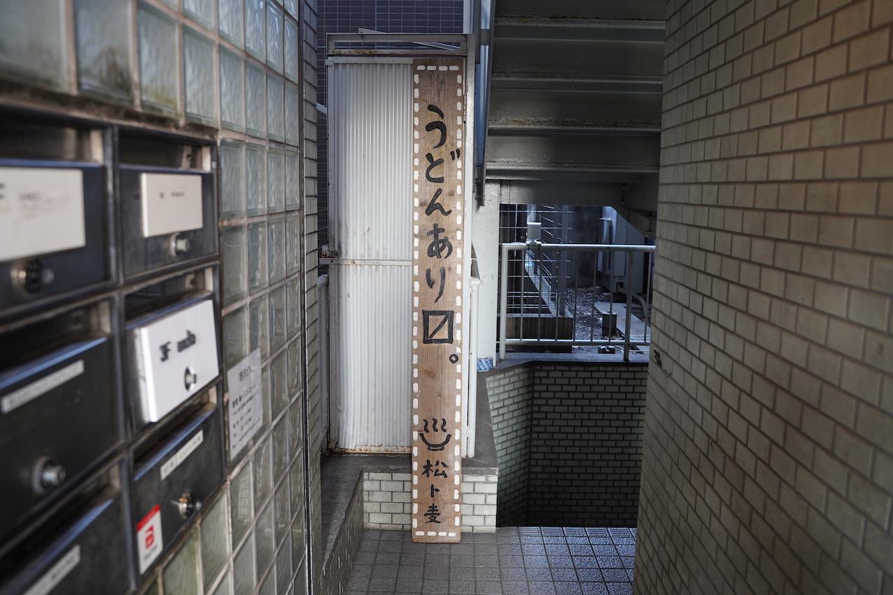 ビル1階にある「うどんあり〼(マス)」の看板横にある階段を地下へと降ると「松ト麦」がある