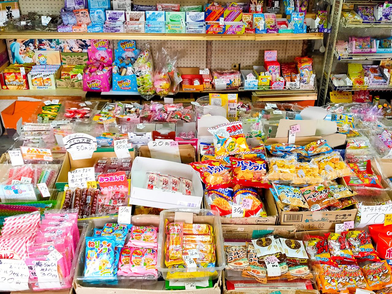 お店にはたくさんの駄菓子の中からどれを買おうかと一生懸命に悩みながら選ぶこどもたちがたくさん