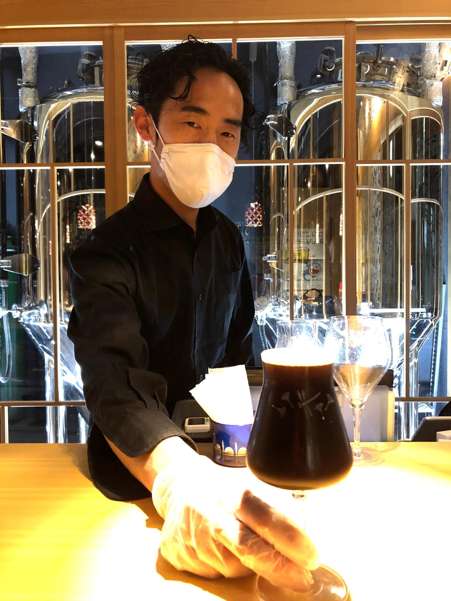 「黒に浮かぶ」をサーブする田上さん