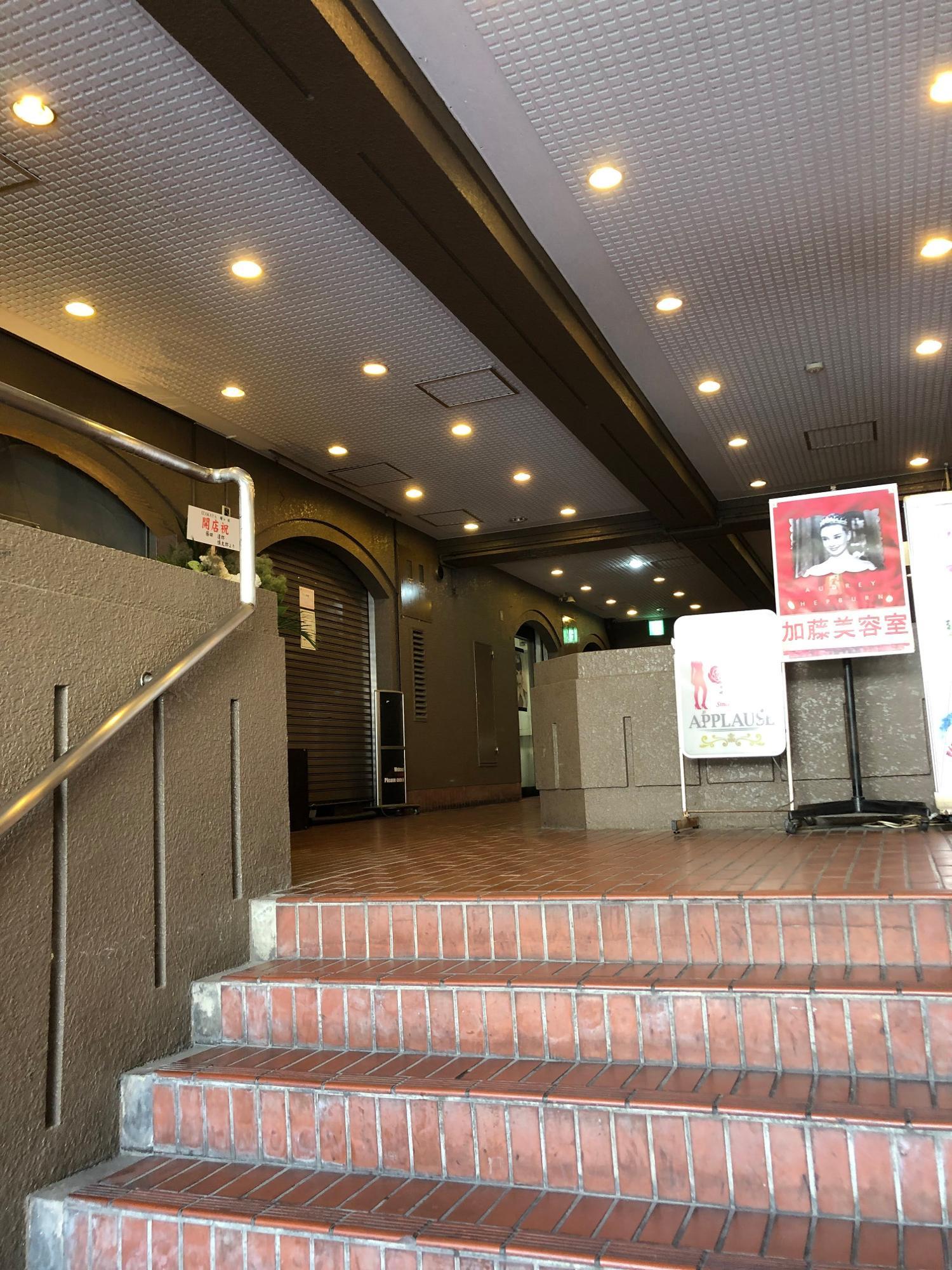 昭和の香りのするこの階段を登った左側にある