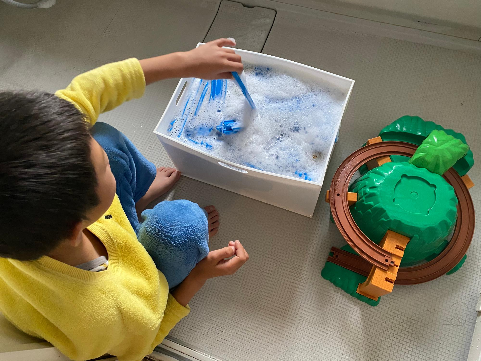 友達に譲る電車のおもちゃを洗う次男