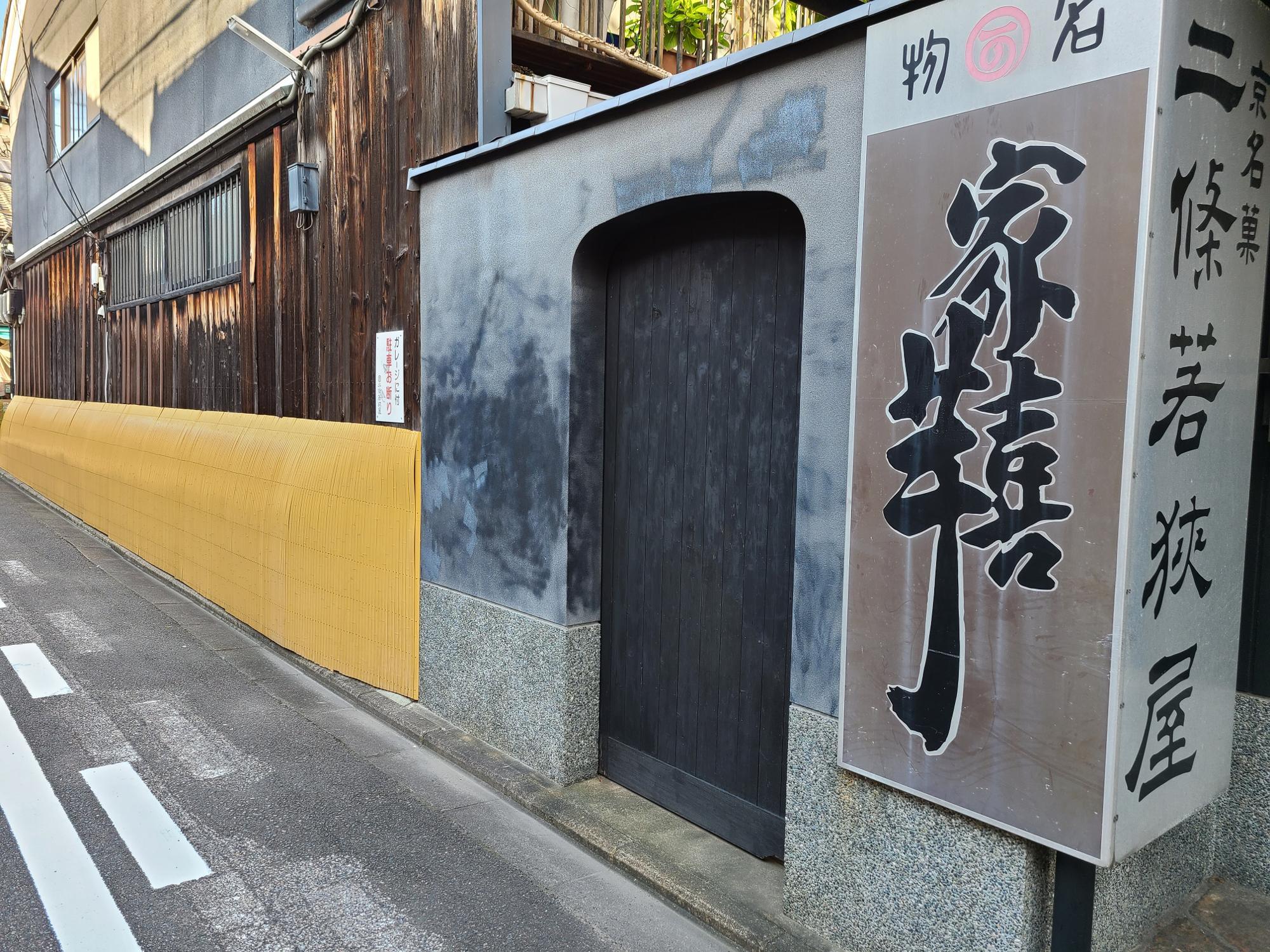昔の看板や犬矢来などに囲まれた旧店舗の外観