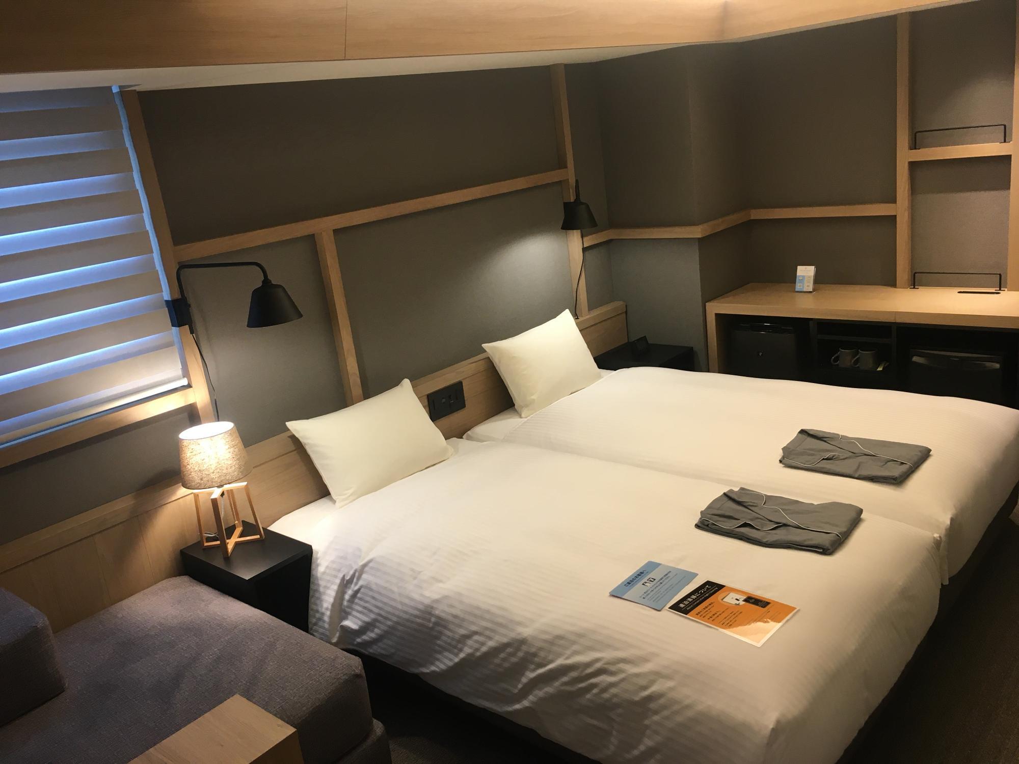 モデレートツインルーム。木の格子がアクセントになっているシンプルな客室