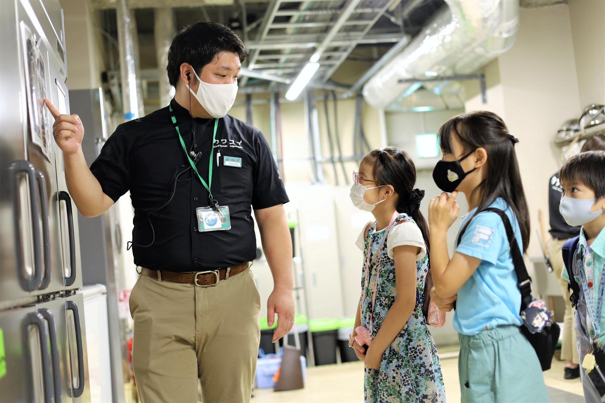 子どもたちにバックヤードの役割について分かりやすく案内する浅野目さん(写真 左)