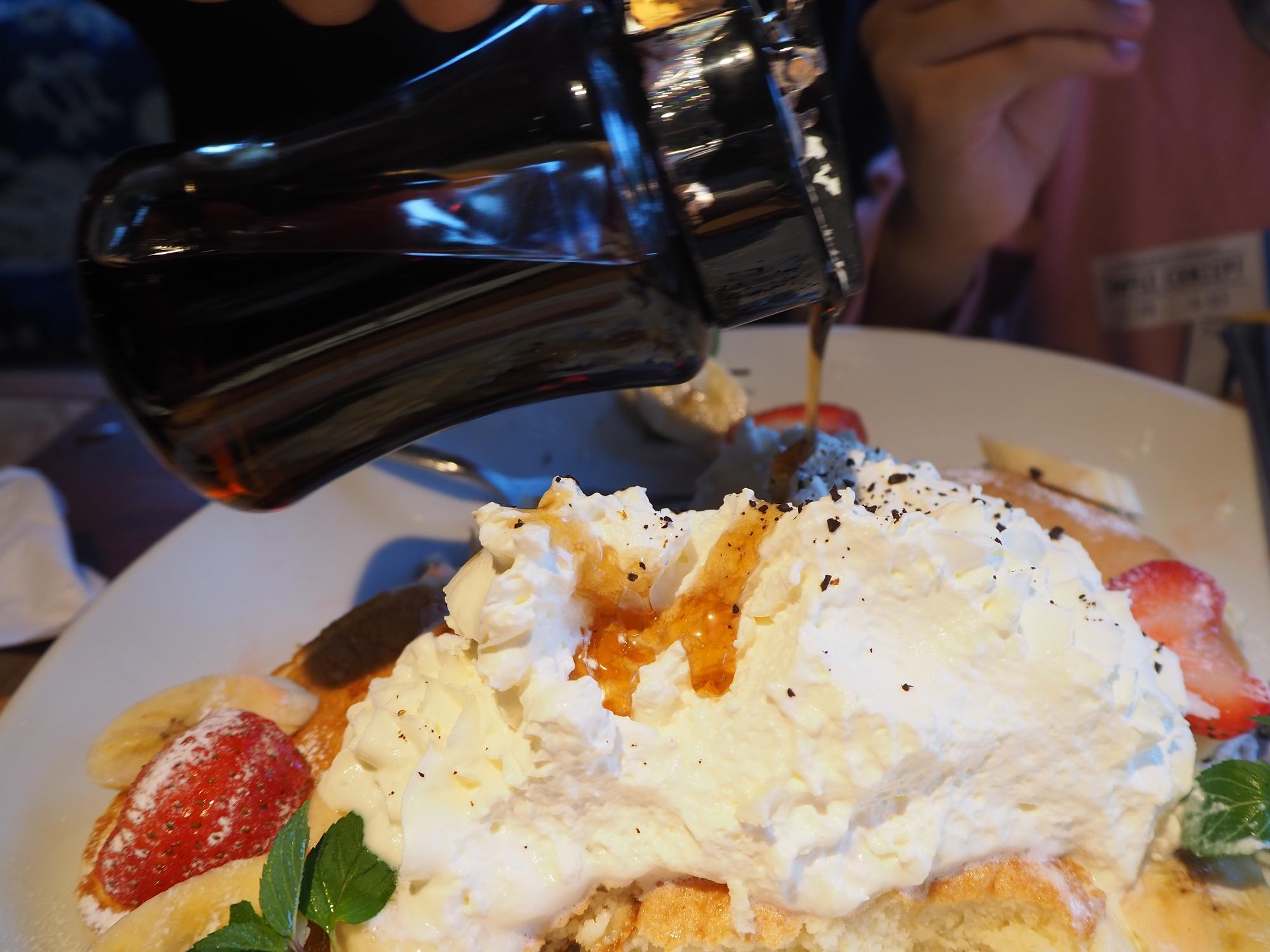 パンケーキに乗っているホイップクリームに、削ったコーヒー豆とメープルシロップをかけて味変するのもオススメ。