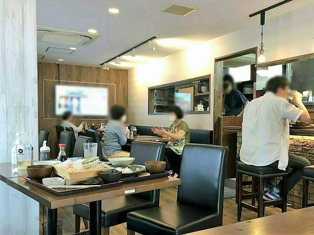 店内はテーブル席のほかカウンター席も。卓上には調味料とアルコール消毒が置いてあります。テレビもあるので、待ち時間の暇つぶし対策も万全です。