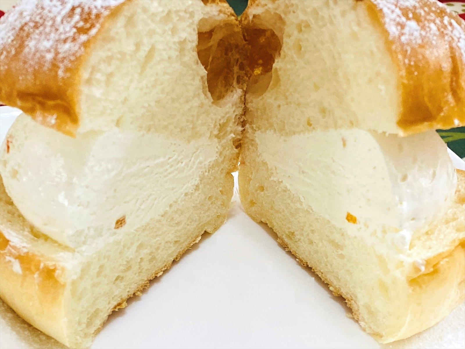 マリトッツォ 断面。やや大きめのパンに、たーっぷりとしたクリームが挟まっているためナイフで半分にカット