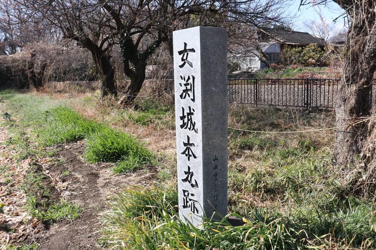 女渕城本丸跡の石碑。あたりは城趾公園になっており、池にのんびいりと釣り糸を垂れる人の姿があった。
