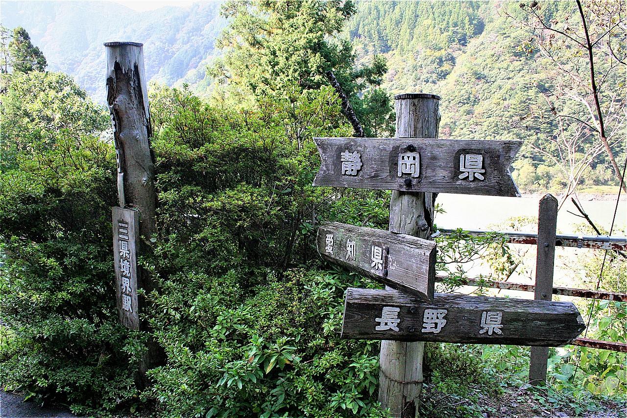 三県境界を表わす碑が立っている。その向こうには天竜川が見える。